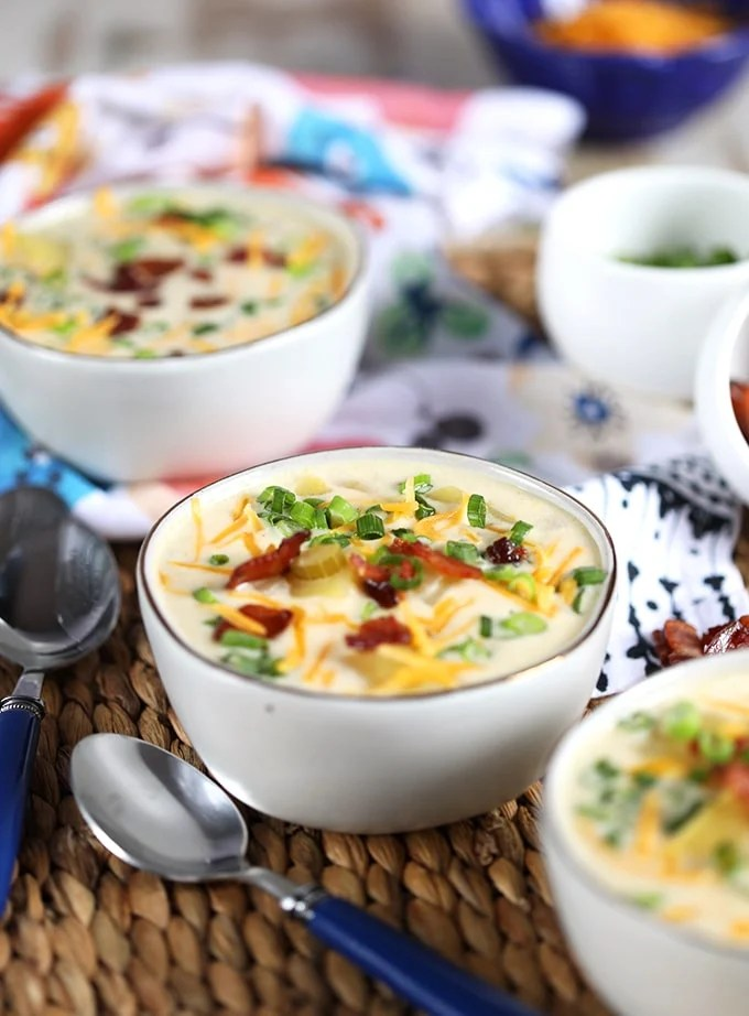 Three white bowls with loaded baked potato soup and a blue spoon.