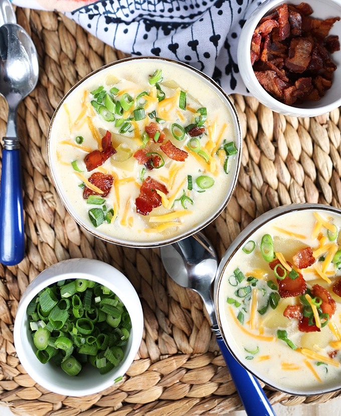 Overhead shot of two white bowls with Loaded Baked Potato Soup with a bowl of scallions and bacon on the side.