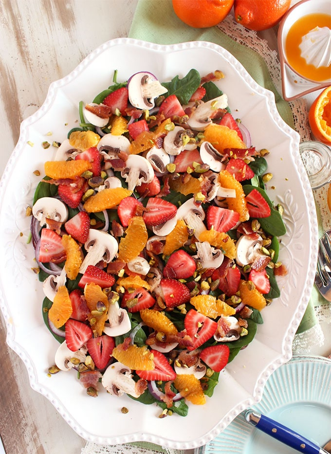 Overhead shot of strawberry spinach salad with oranges on a white oval platter.