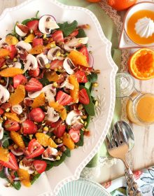 Overhead shot of strawberry spinach salad on a white oval platter.