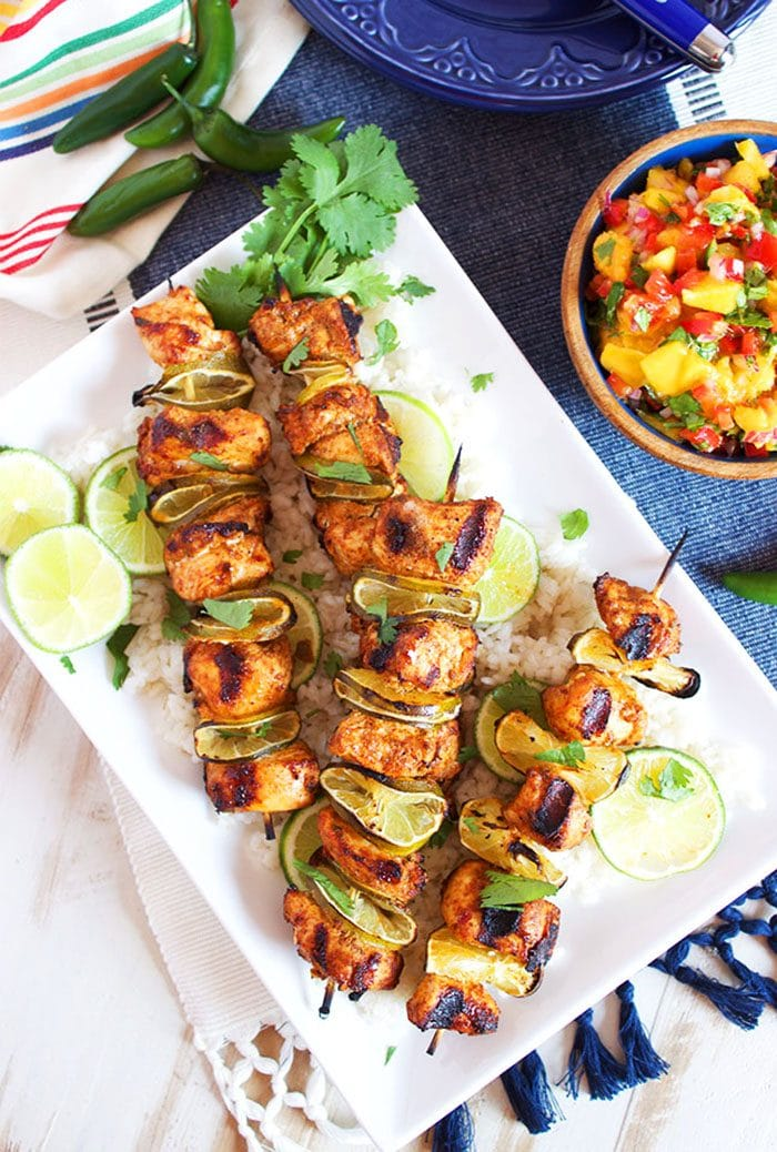 Overhead shot of chili lime chicken kabobs on a white platter.