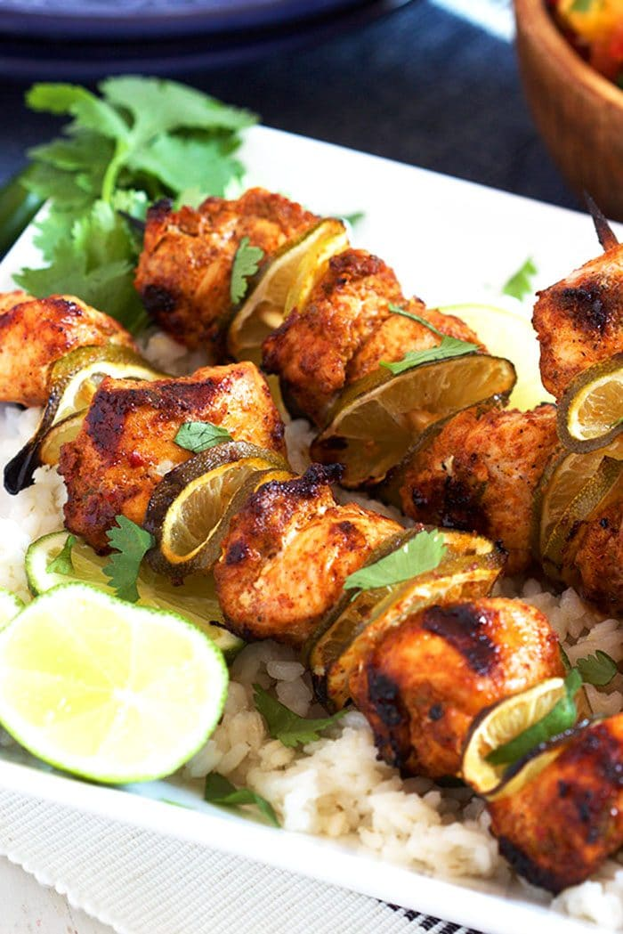 Chili Lime Chicken Kabobs on a white platter with rice and a lime.