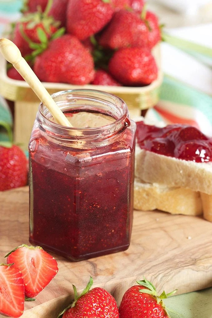 Strawberry Jam in a jelly jar with a small wooden spoon and a basket of strawberries in the background.