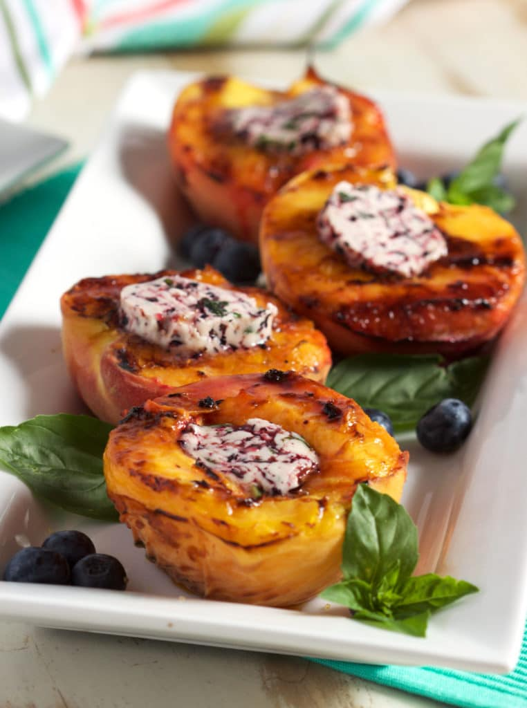 A quick and easy Grilled Peach recipe topped with an easy to make blueberry basil butter from TheSuburbanSoapbox.com.