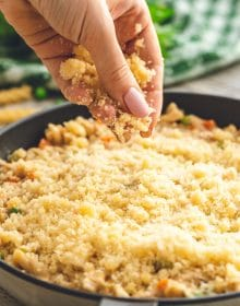 Bread crumbs being sprinkled on tuna noodle casserole.