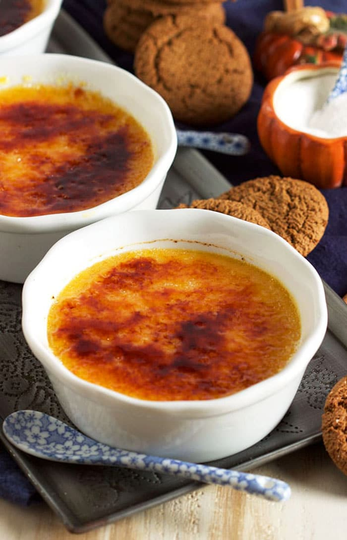 Pumpkin creme brulee in a white ramekin with a blue and white spoon and a pile of gingersnap cookies.