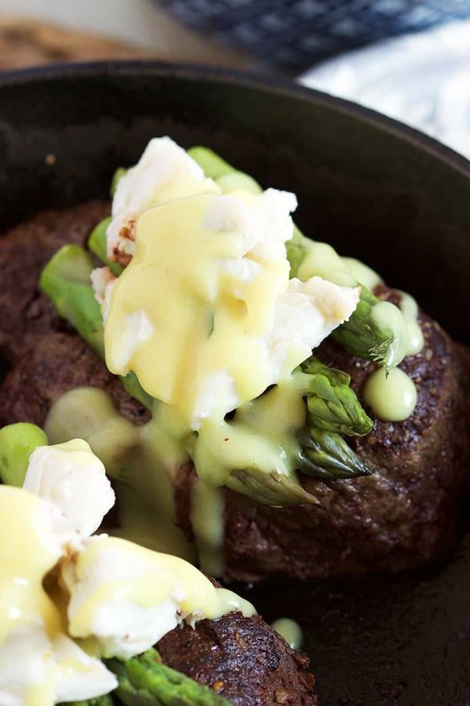 Filet Mignon with asparagus, crab and béarnaise in a cast iron skillet.