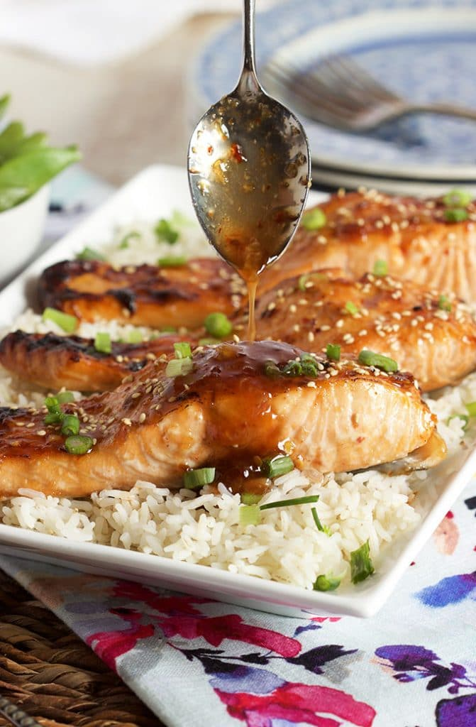 Sweet Chili Orange Glazed Salmon on a bed of rice with sauce being drizzled over top.