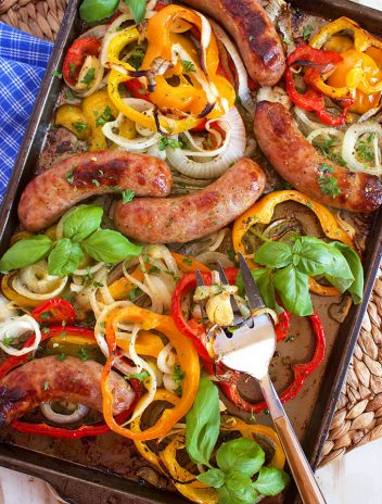 Sausage peppers and onions on a sheet pan with basil on a white board.