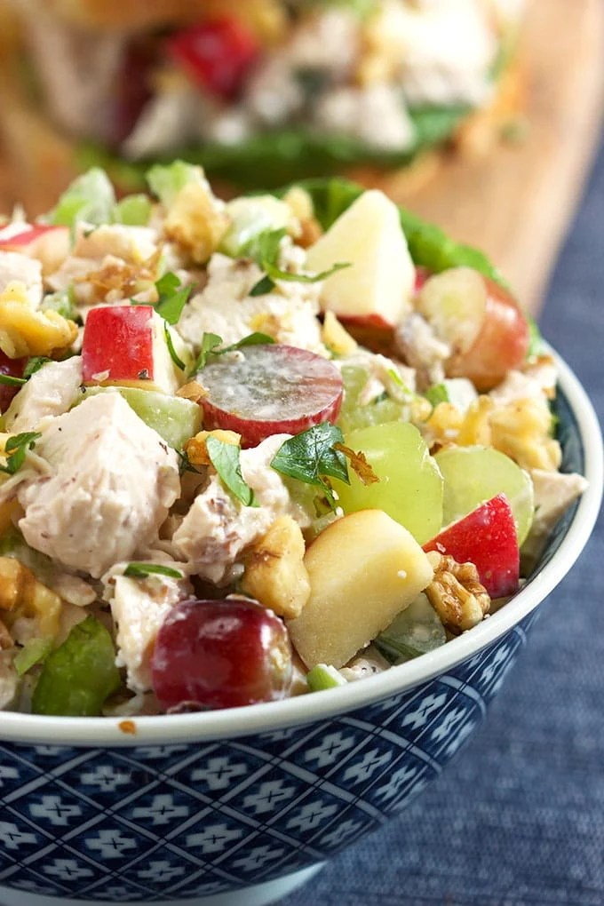 Chicken Waldorf Salad in a blue and white bowl on a blue napkin.