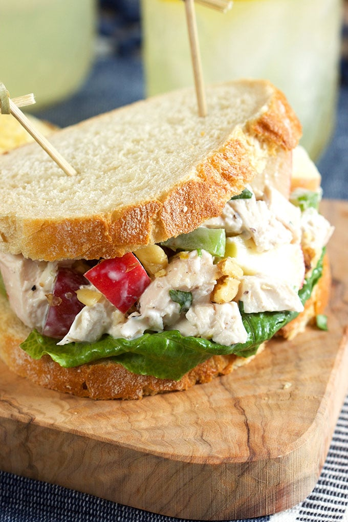 Chicken Waldorf Salad sandwich on an olive wood board with toothpicks.