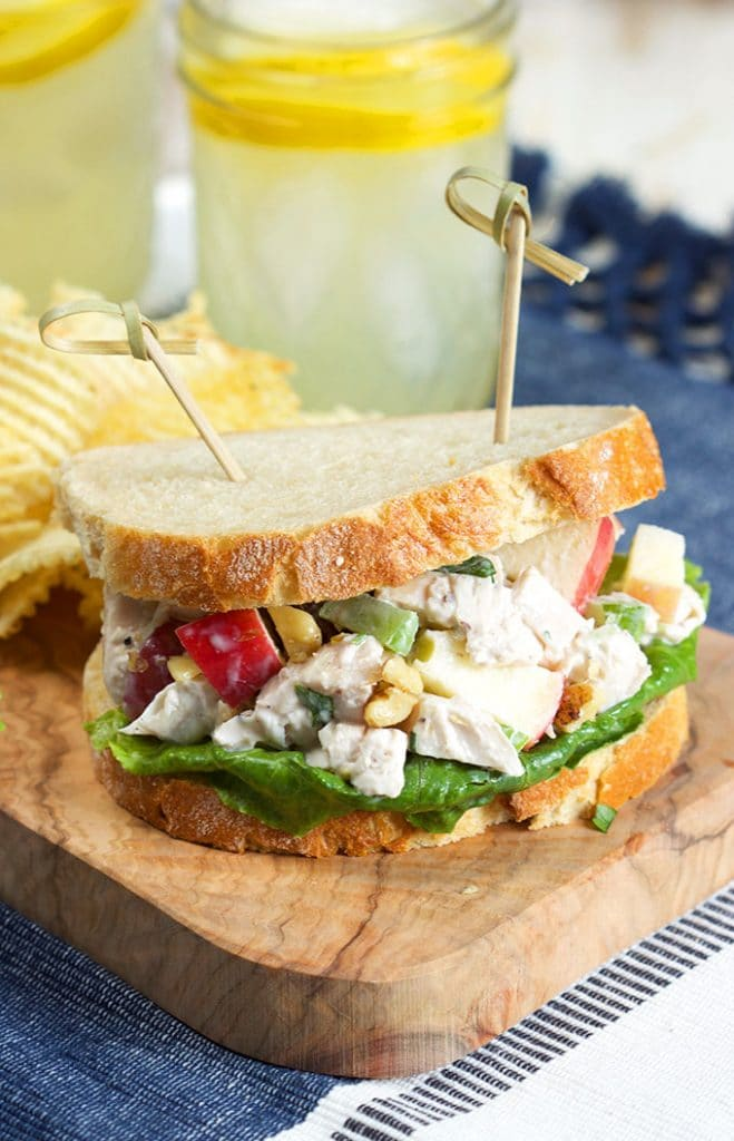 Chicken Waldorf Salad sandwich on a wooden board with potato chips.