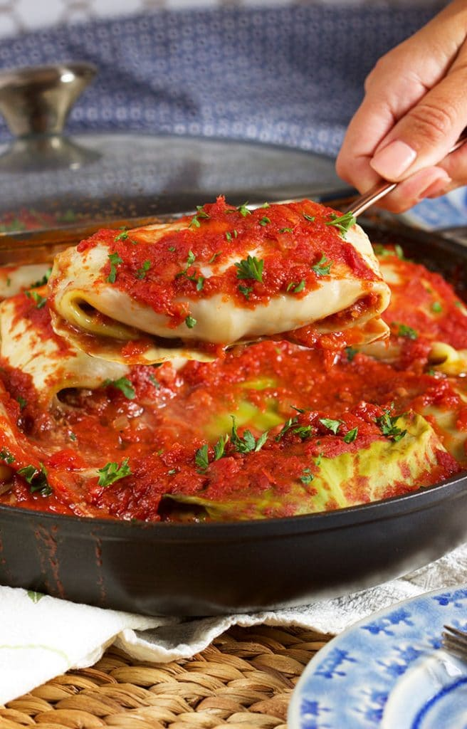 Stuffed cabbage rolls being served from a black pan.
