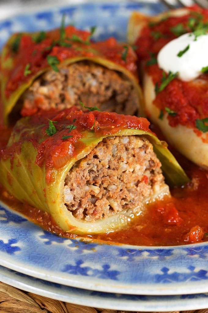 close up of the inside of a stuffed cabbage roll on a blue plate.