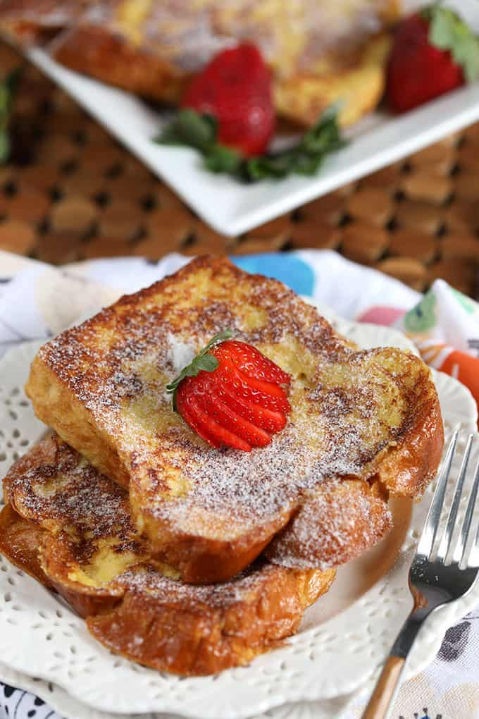 Two slices of French toast with a strawberry on a white plate from TheSuburbanSoapbox.com