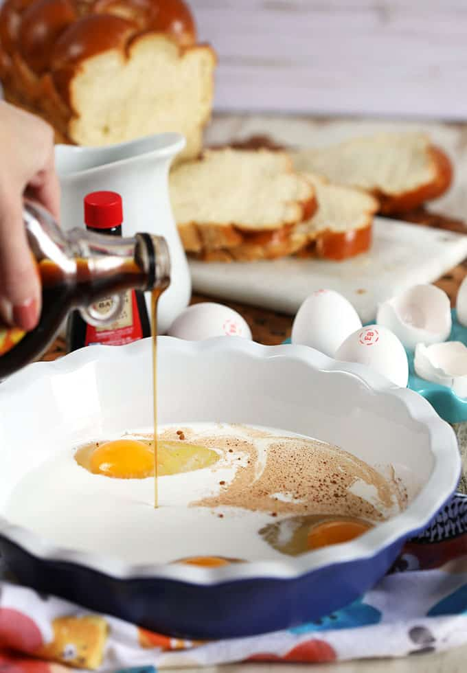 Adding maple syrup to the very best French toast recipe ingredients in a blue pie plate from TheSuburbanSoapbox.com