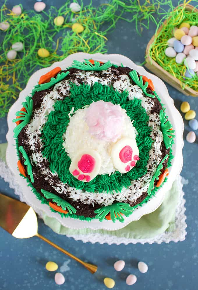 Overhead view of Oreo Ice Cream Cake decorated with white bunny butt with pink cotton candy tail and chocolate carrots on a blue background. From TheSuburbanSoapbox.com