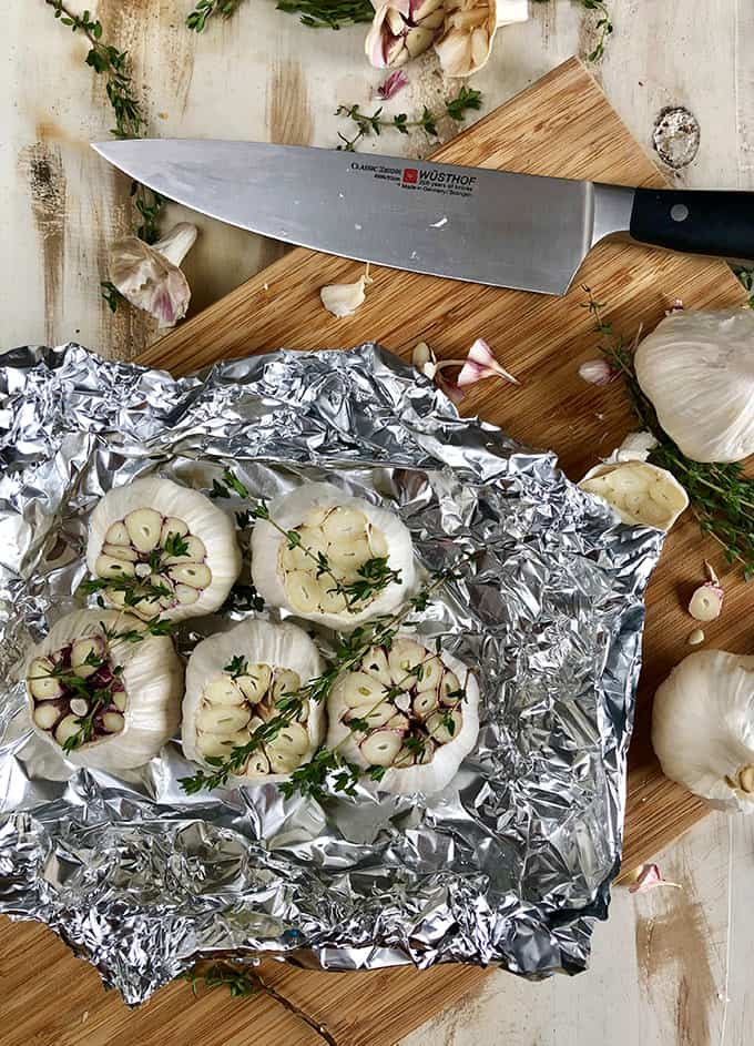 Sliced Garlic bulbs with thyme in foil with chef's knife. | TheSuburbanSoapbox.com
