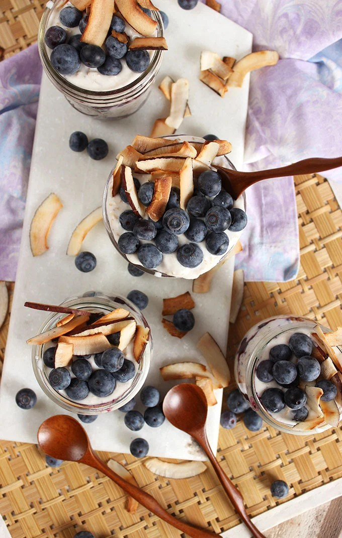 Easy to make toasted coconut overnight oats with blueberries in jars on a marble board. From TheSuburbanSoapbox.com