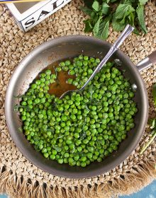 Brown Butter Sweet Peas with Mint in a skillet with a spoon and a salt box from TheSuburbanSoapbox.com