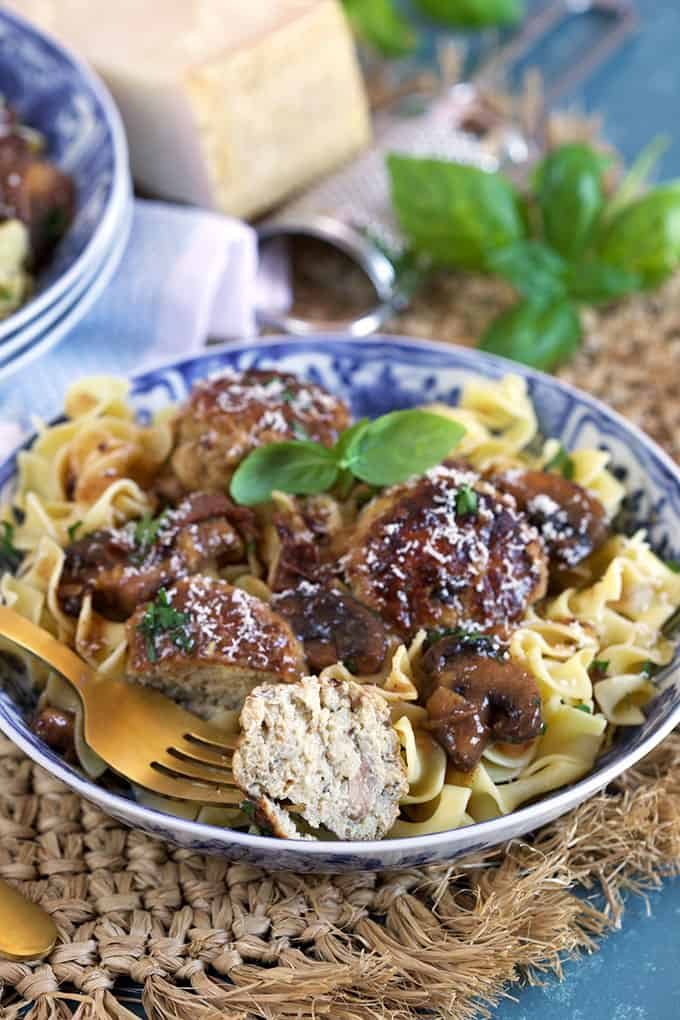 One Pot Chicken Marsala Meatballs recipe over egg noodles with a bite taken from a meatball on a blue and white bowl from TheSuburbansoapbox.com
