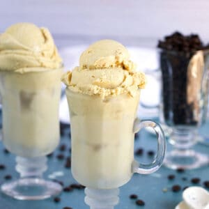 Homemade Coffee Ice Cream in an Irish coffee glass with a glass of coffee beans and white ceramic spoons on a blue background from TheSuburbanSoapbox.com
