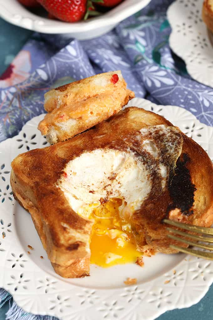 Pimento cheese Grilled Cheese Egg in a Hole Sandwich with a bite take on a white plate with blue background from TheSuburbanSoapbox.com