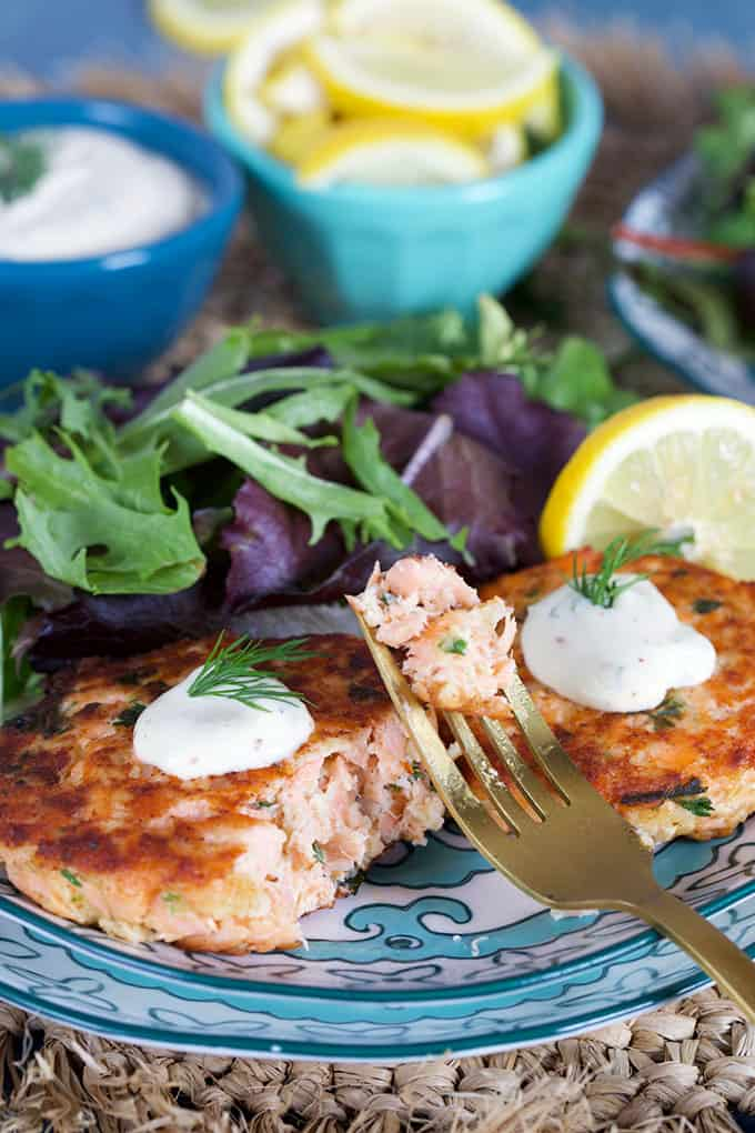 Salmon Cake recipe on a decorative plate with a fork and lemons from TheSuburbansoapbox.com