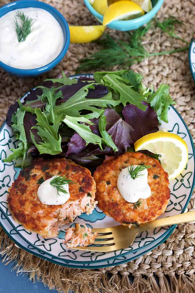 Overhead shot of Salmon Cakes Recipe with Lemon Dill Sauce on blue and white plate with sauce in a blue bowl from TheSuburbanSoapbox.com