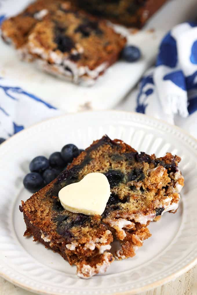 A slice of Blueberry Banana Bread with a heart shaped butter pat on a white plate from TheSuburbanSoapbox.com