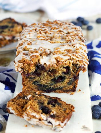 Blueberry Banana Bread with two slices on a white marble board from TheSuburbanSoapbox.com