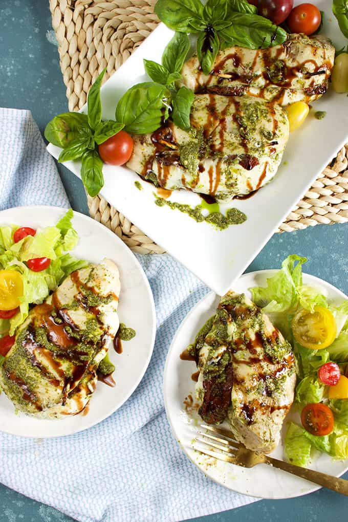 Overhead shot of Grilled Caprese Stuffed Chicken on a white platter and two plates with salad from TheSuburbanSoapbox.com