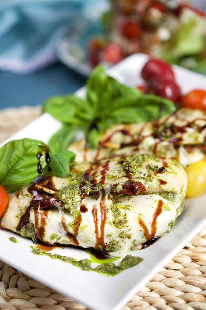 Grilled Caprese Stuffed Chicken on a white platter with fresh basil and tomatoes from TheSuburbanSoapbox.com