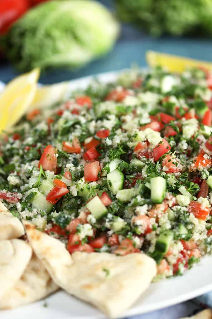 Side shot of Cauliflower Rice Tabbouleh Salad on a white platter with pita bread from TheSuburbanSoapbox.com