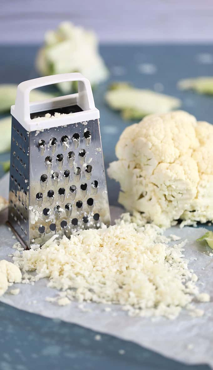 Cauliflower rice made with a box grater with a head of cauliflower on a blue background from TheSuburbanSoapbox.com
