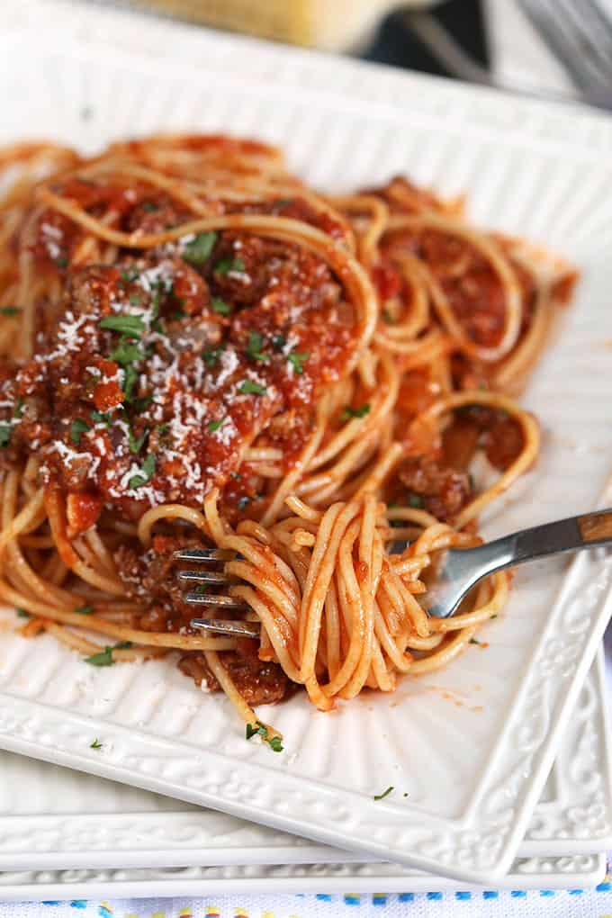 Spaghetti with Easy Italian Meat Sauce recipe on a white square plate with a fork from TheSuburbanSoapbox.com