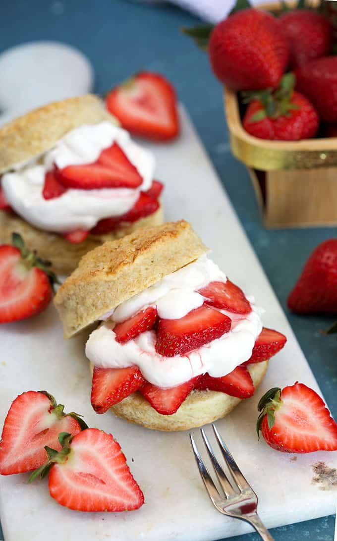 Two of the BEST Strawberry Shortcake recipe on a white marble board on a blue background from thesuburbansoapbox.com