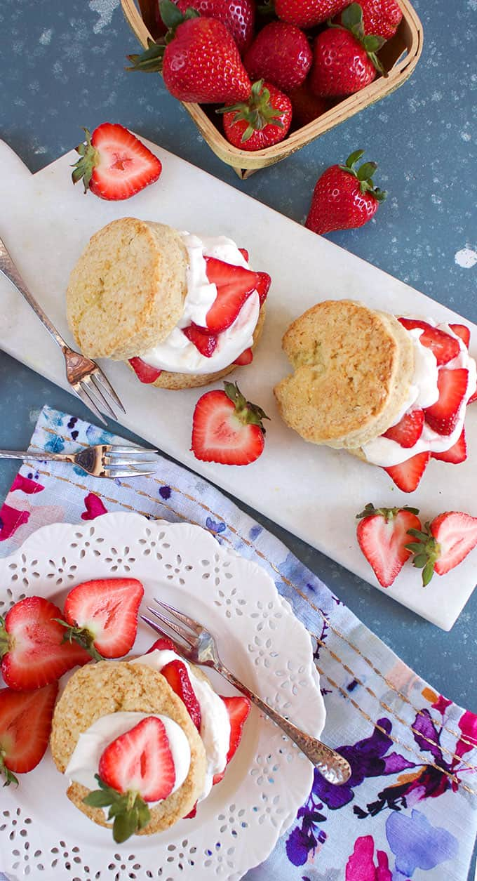 Overhead shot of three of the Very BEST Strawberry Shortcake on a white plate and marble board on a blue background from TheSuburbanSoapbox.com