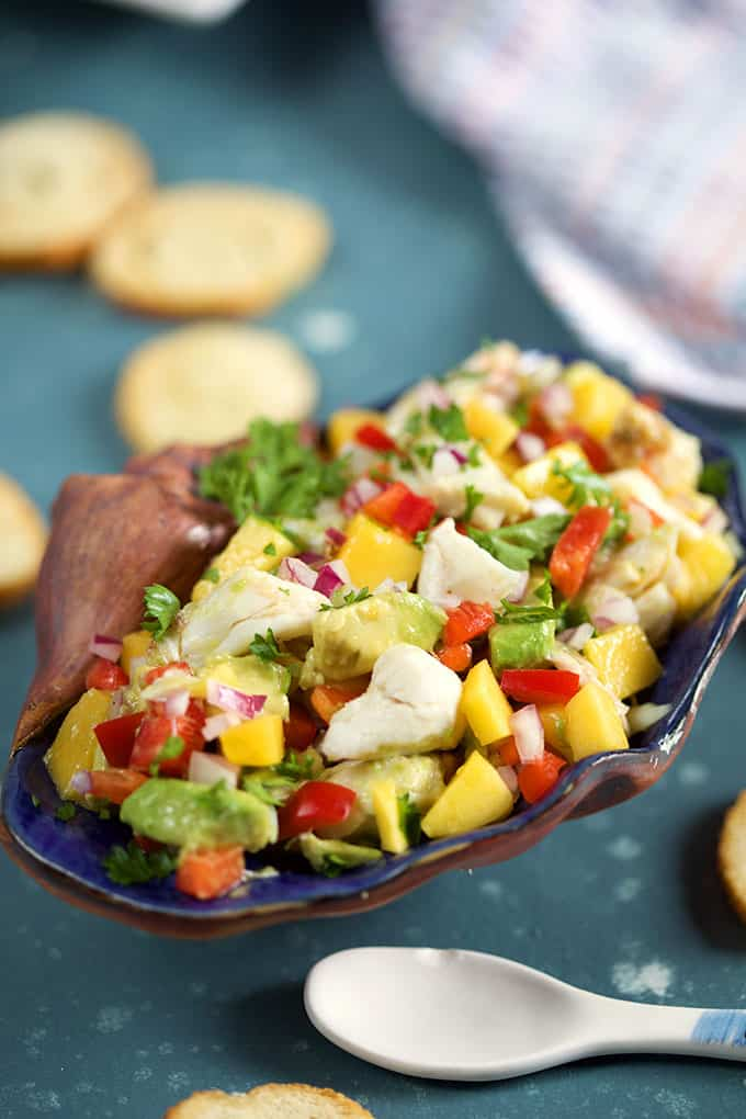 Mango Crab Avocado Salad in a shell on a blue background from TheSuburbanSoapbox.com