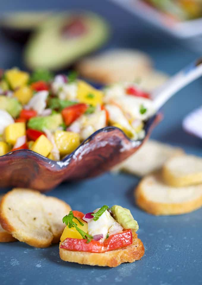 Mango Crab Avocado Salad on a crostini with shell bowl of salad in background from TheSuburbansoapbox.com