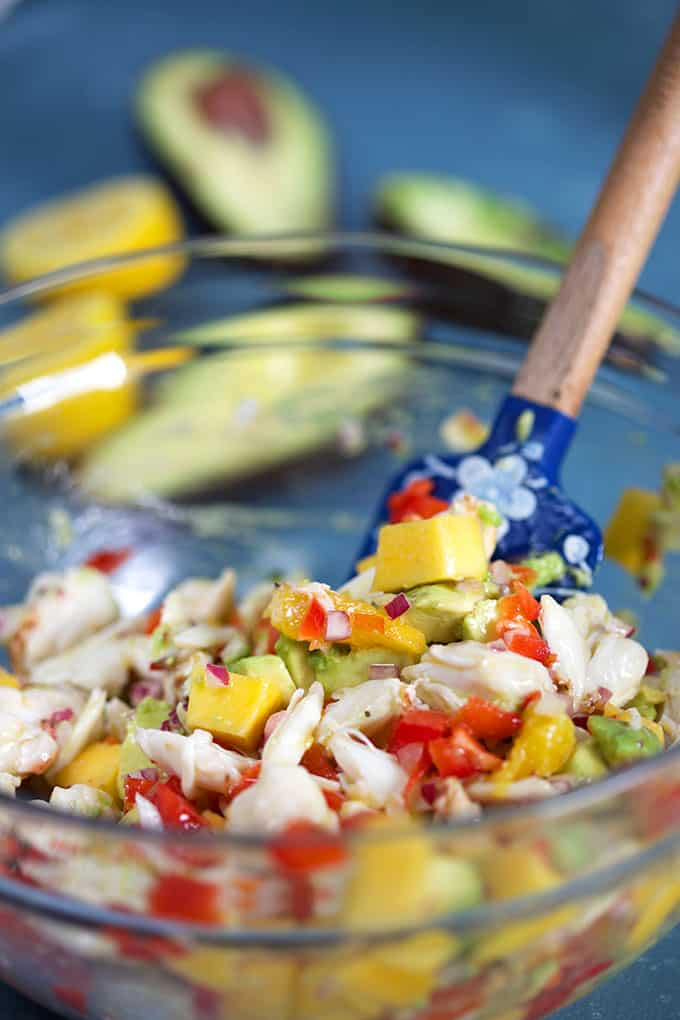 Mango Crab Avocado Salad in a glass bowl with a blue spatula stirring the salad from TheSuburbansoapbox.com