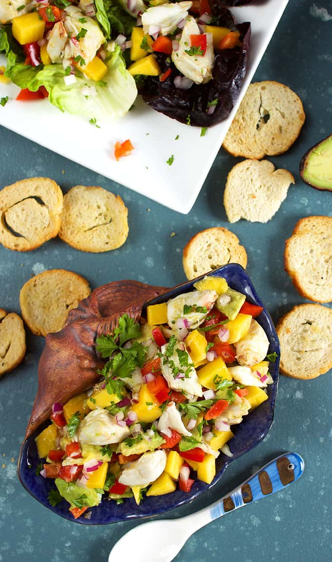 Overhead shot of Mango Crab Avocado Salad in a shell on a blue background with crostini from TheSuburbansoapbox.com