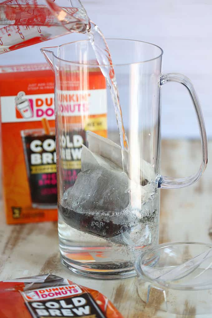 Clear pitcher with Dunkin Donuts Cold Brew packet and water being added to the pitcher from TheSuburbanSoapbox.com