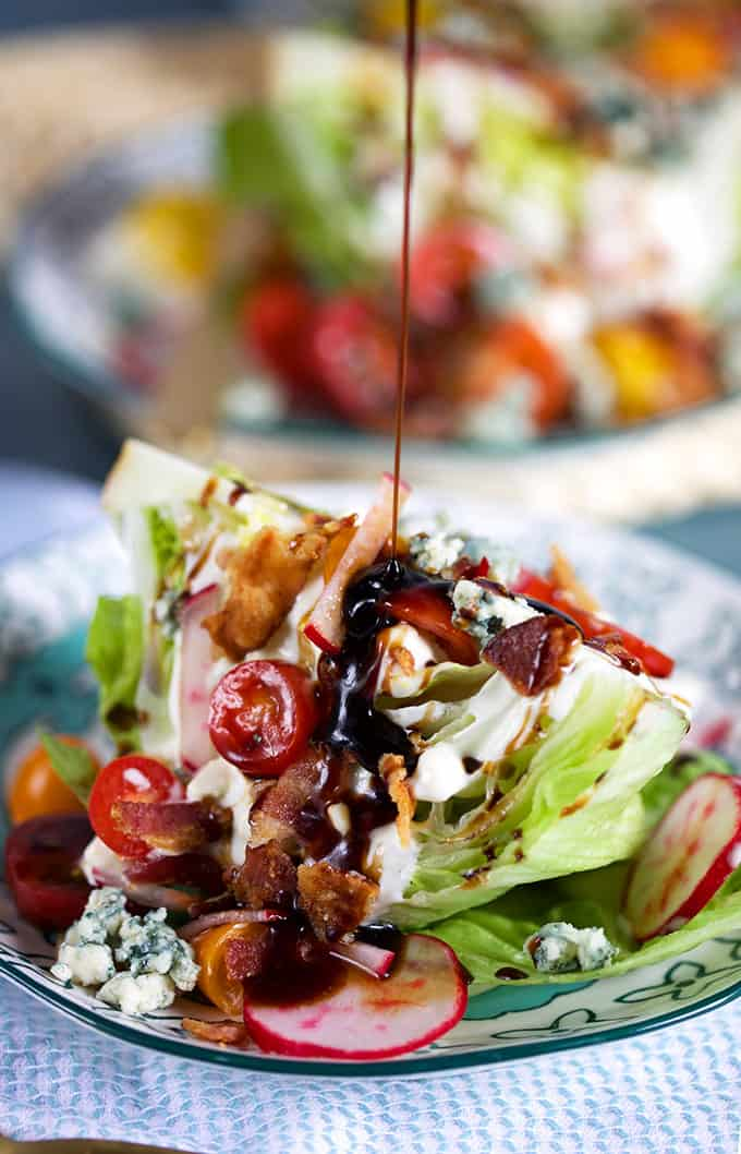 Loaded iceberg wedge salad with a balsamic glaze being drizzled on top from TheSuburbanSoapbox.com