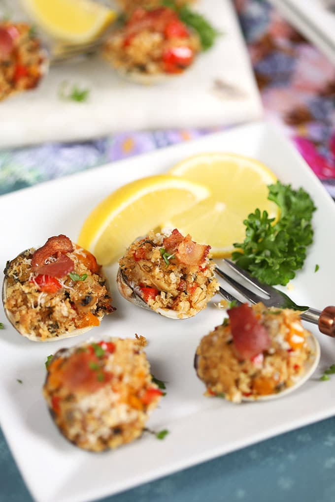 Baked Clams Casino on a white plate with lemons and parsley from ThesuburbanSoapbox.com