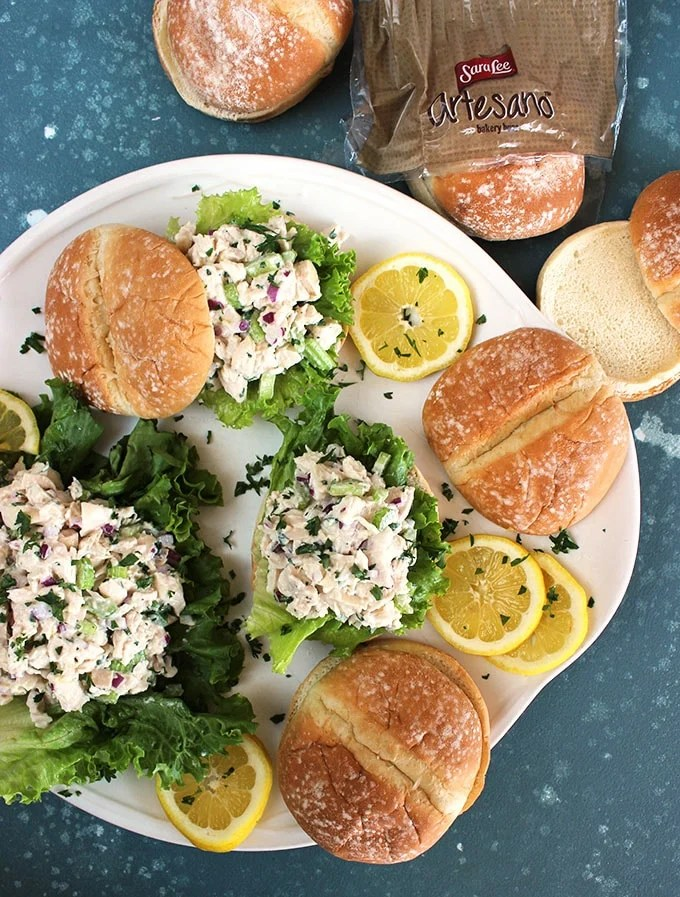 Overhead shot of lemon tarragon chicken salad sandwiches on a white platter with a blue background from TheSuburbansoapbox.com