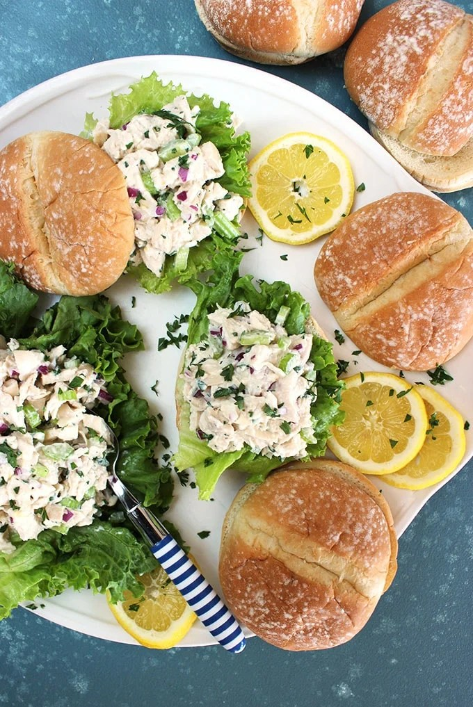 Overhead shot of lemon tarragon chicken salad on rolls on a white platter with a blue background from TheSuburbansoapbox.com
