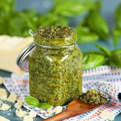 Basil pesto in a glass jar with basil in the background and wooden spoon from TheSuburbanSoapbox.com