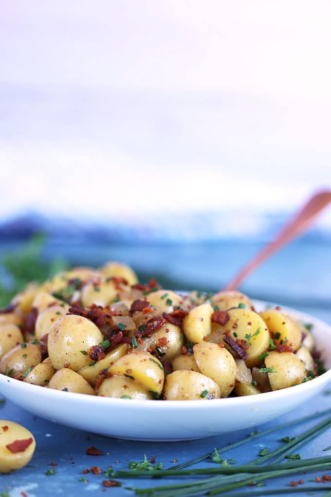 Warm German Potato Salad in a white bowl with a copper spoon from TheSuburbanSoapbox.com