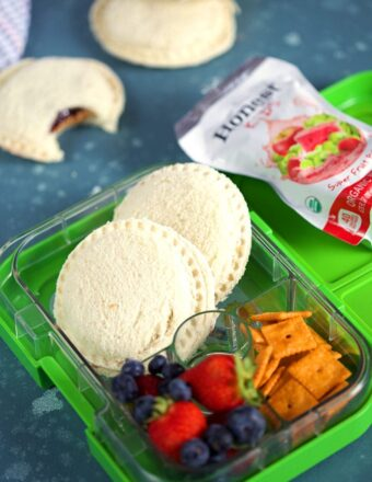 Homemade Peanut Butter and Jelly Uncrustables in a green lunchbox with fruit and crackers on a blue background from ThesuburbanSoapbox.com